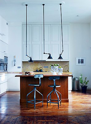 Vintage pendant lamps above wooden counter and bar stools in open-plan kitchen - p1183m995925 by Ranek, Lars