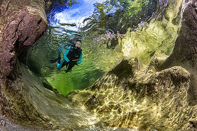 Austria, Salzkammergut, river Weissenbach, female scuba diver in a wild mountain river - p300m2104146 by Herbert Meyrl