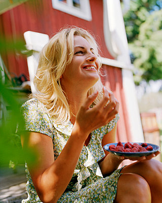 A smiling woman eating strawberries Sweden - p31222290f by Per Eriksson