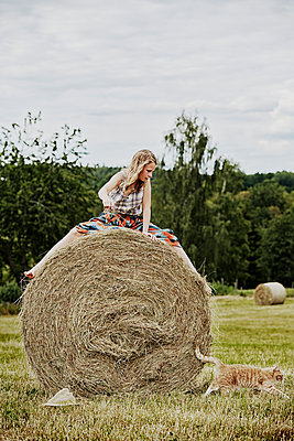 Girl sitting on bale of hay - p312m2091932 by Anna Kern