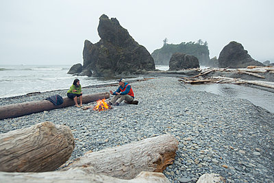 Two hikers enjoy a campfire on a beach in the Pacific Northwest. - p343m1217985 by Matt Andrew