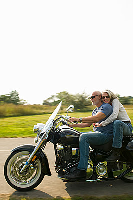 Older couple riding motorcycle on rural road - p555m1411192 by Alberto Guglielmi