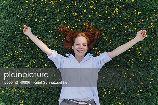 Portrait of happy redheaded woman lying on a flower meadow - p300m2140836 von Kniel Synnatzschke
