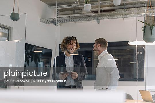 Two happy businessmen talking in office - p300m2166761 by Kniel Synnatzschke