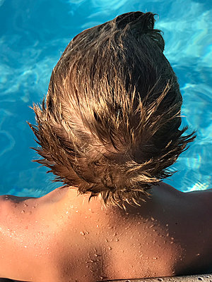 Boy's wet hair and shoulders in a pool - p1048m2025651 by Mark Wagner