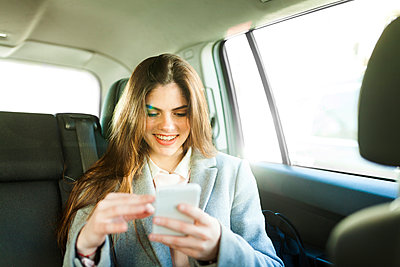 Portrait of smiling young businesswoman sitting on backseat of a car looking at cell phone - p300m1587778 by Valentina Barreto