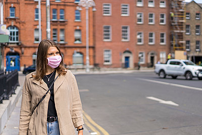 Young woman wearing protective face mask standing on street in city - p300m2220543 by Boy photography