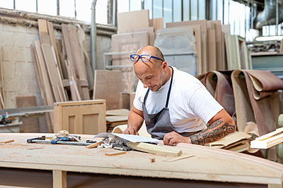 Carpenter reading design in paper while standing at workbench in factory - p300m2221066 by Emma Innocenti