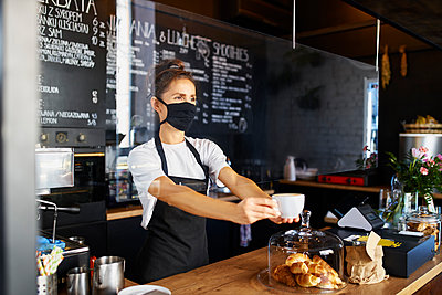 Waitress wearing protective face mask while giving coffee at cafe - p300m2225071 by Bartek Szewczyk