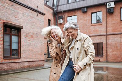 Cheerful female friends sharing headphones while listening music - p300m2276651 by Katharina und Ekaterina