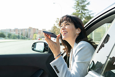 Female professional sending voicemail while looking away in car - p300m2282157 by Jose Carlos Ichiro