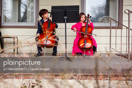 Two children sit outside in fancy dress playing cellos on porch - p1166m2250671 by Cavan Images
