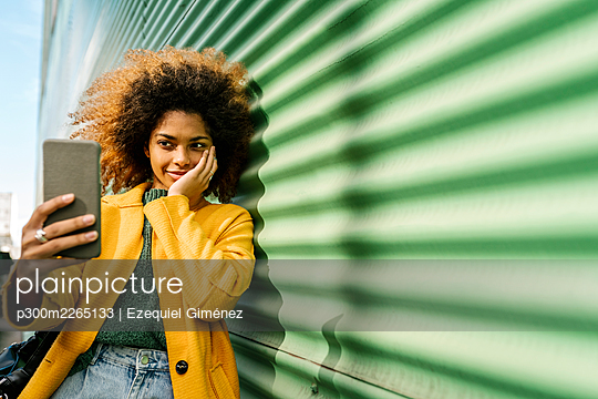 Smiling Afro woman with hand on cheek taking selfie through mobile phone while leaning on green wall - p300m2265133 by Ezequiel Giménez