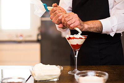 Crop chef adding cream to dessert - p1166m2124223 by Cavan Images