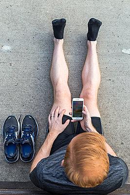 Jogger benutzt Smartphone nach Training. - p1396m1463548 von Hartmann + Beese
