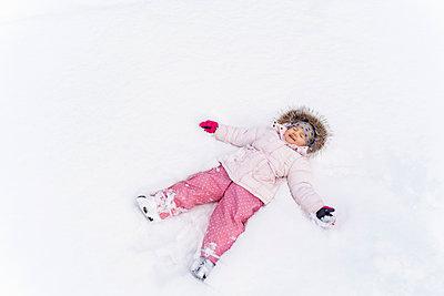 Cute little girl lying in snow in winter making a snow angel - p300m2083320 by Daniel Ingold