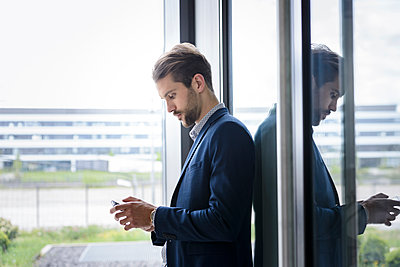 Young businessman using smartphone at the window - p300m2154624 by Buero Monaco