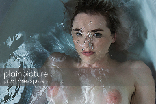 Young woman in the bathtub, portrait - p1488m2259840 by Sid Miller