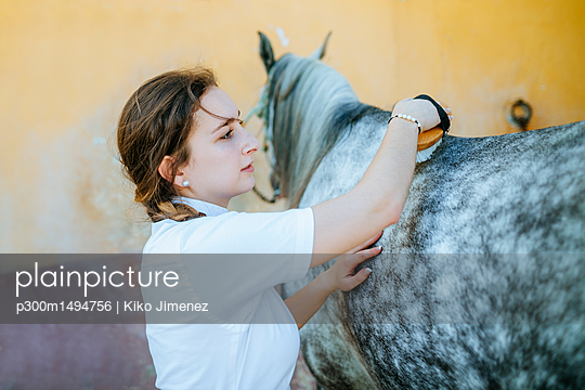 plainpicture | Photo library for authentic images - plainpicture p300m1494756 - Young woman grooming horse - plainpicture/Westend61/Kiko Jimenez