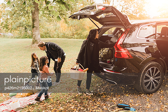 Family unloading luggage from electric car on field during picnic - p426m2195002 by Maskot