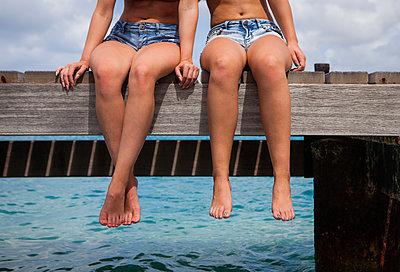 Zwei Freundinnen sitzen zusammen auf Holzsteg - p045m2027619 von Jasmin Sander