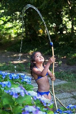 Mädchen spielt mit einem Gartenschlauch - p1231m2013521 von Iris Loonen