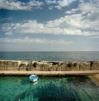 A wooden rowing boat moored in a small harbour in Castro, Puglia, Italy - p429m802672 by Cultura