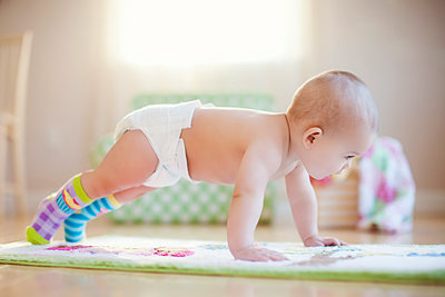 Mixed race baby girl playing on floor - p555m1311405 by Shestock