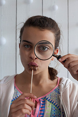 Girl looking through a magnifying glass - p596m951206 by Ariane Galateau