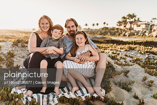 Portrait of family of four sitting on blanket at beach during sunset - p1166m2136577 by Cavan Images