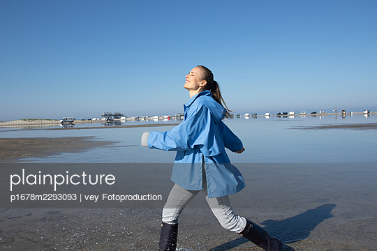 Woman taking a walk by the sea - p1678m2293093 by vey Fotoproduction