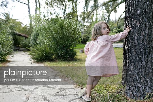 Portrait of little girl leaning against tree trunk in garden - p300m1587377 von Katharina Mikhrin