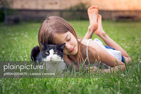Little girl cuddling with cat on a meadow - p300m2004679 von Larissa Veronesi