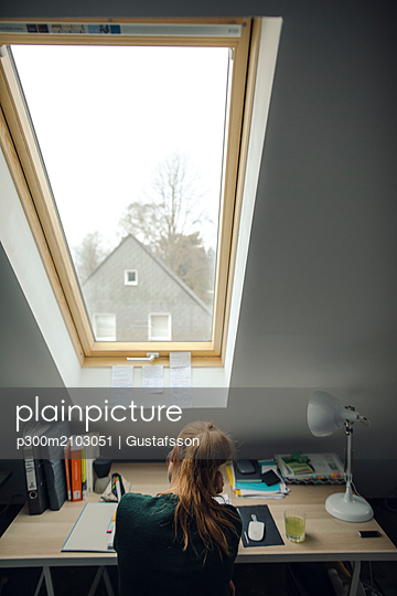 Rear view of young woman sitting at desk in attic - p300m2103051 by Gustafsson