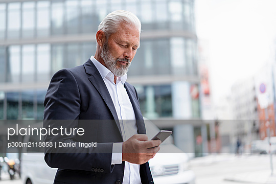 Mature businessman using cell phone in the city - p300m2118858 by Daniel Ingold