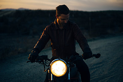 Man riding illuminated motorcycle on field - p1166m1164291 by Cavan Images