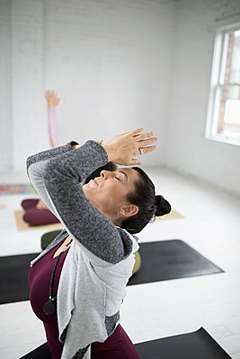 Woman practicing yoga backbend in yoga class - p1192m1583316 by Hero Images