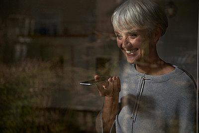 Portrait of smiling senior woman behind windowpane using smartphone - p300m2180230 by Stefanie Aumiller