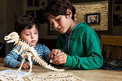 Boy showing brother way to build wooden dinosaur - p429m2127797 by Bonfanti Diego
