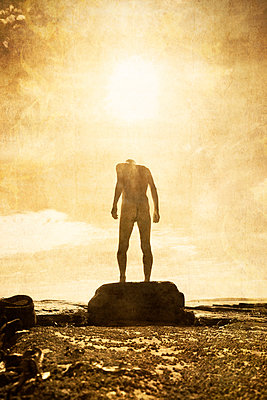 Naked man standing on rock at seaside - p597m2008081 by Tim Robinson