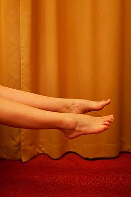 Beine einer Frau in der Luft vor einem orange-farbenem Vorhang - p795m2087489 von JanJasperKlein
