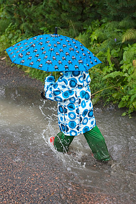 High Angle View Of A Boy Walking With Umbrella - p816m913501 by Nils-Erik Bjørholt