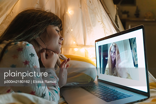 Girl lying on bed at night skyping with her mother working outside home - p300m2180162 by Eloisa Ramos