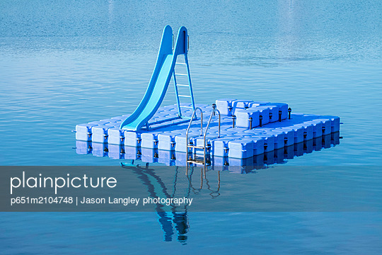 Blue dock with water slide floating in blue lake, Hamburg Stadtpark, Hamburg, Germany - p651m2104748 by Jason Langley photography