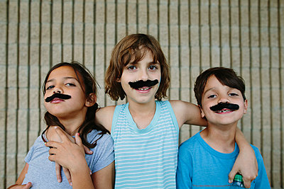 Portrait of happy siblings with artificial mustache against wall - p1166m1406847 by Cavan Images