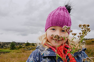 Portrait of cute girl with wildflowers at field - p1166m1512708 by Cavan Images