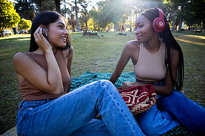 Two teenage girls with earphones listen to music in the park - p1640m2259874 by Holly & John