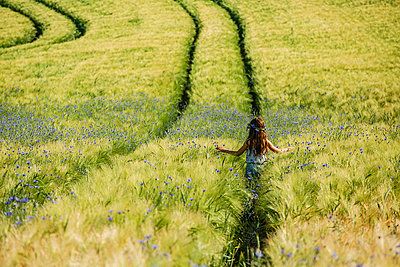 Carefree girl walking in sunny, idyllic rural field with wildflowers - p301m2075665 by Sven Hagolani