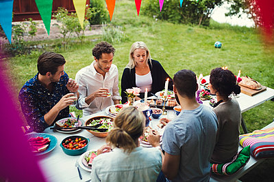 High angle view of friends enjoying dinner at garden party - p426m1226417 by Maskot
