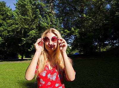 Junge Frau hält Sonnebrille vor das Gesicht - p432m1586255 von mia takahara
